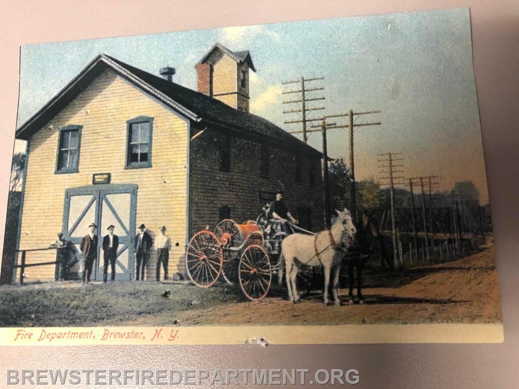 Photo #1 The previous Firehouse on Railroad Avenue opposite the Baptist church  Notice the hose reel cart.
